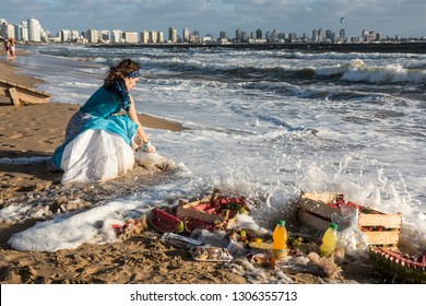 Maldonado, Uruguay - February 2, 2019: Woman from the Umbanda church brings fruits and sweets to Orisha Yemanja (Iemanja) on the Playa Mansa beach in Punta del Este