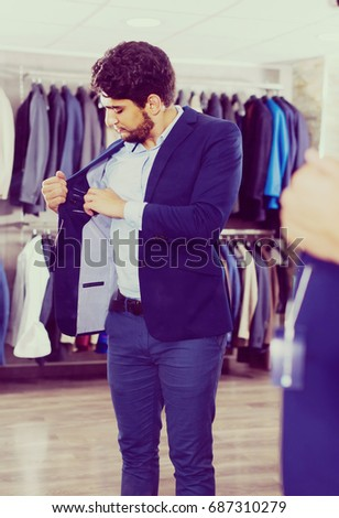 a33ce758ff99f5 Male 25-33 years old is trying on jacket in front of the mirror in