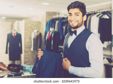 Male 28-36 years old is demonstrating image in waistcoat with butterfly in shop.