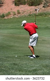 Male about to hit ball from the fairway (towards camera), focus on golfer