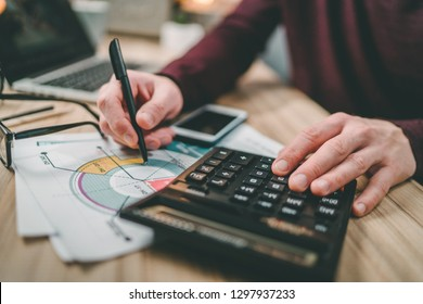 Male accountant working home making calculations. Savings, finance, economy concept.