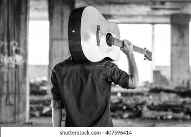 Male with acoustic guitar outdoor, Black and white photo