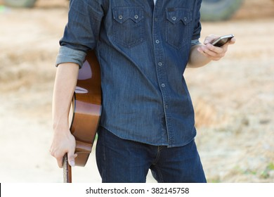 Male with acoustic guitar and using mobile smart phone