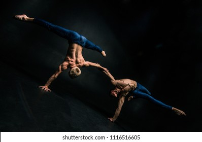 Male acrobatic duo performs a complicated balancing act on a dark background