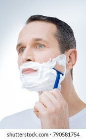 Male activity. Serious handsome brutal man holding a razor and shaving while caring about his appearance