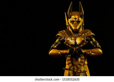 a male actor in a suit of an Egyptian mythology character, the golden deity Jackal Anubis, twists buugeng in yellow light on a black background