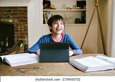 Männlicher Jugendlicher lächelt von der Kamera, während er von zu Hause während der Quarantäne studiert - Covid 19 - Bestellungen - Schule