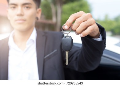 Male adult businessman in a suit  and holding a car key in his hand . White cars at the background