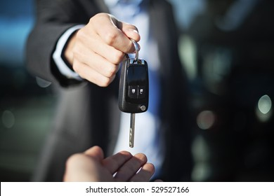 male adult dealer hand giving car keys to female person, close-up photo outdoor, sunny day, caucasian man in suit
