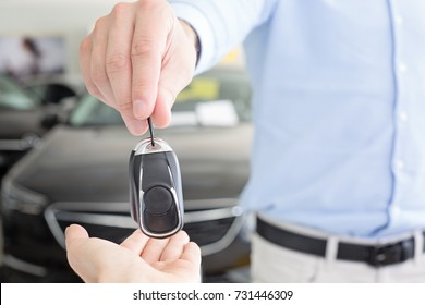 Male adult dealer hand giving car keys to female person, close-up photo taken indoors, cars at the background