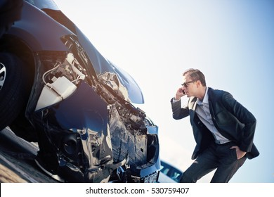 Male adult man in a black winter coat and sunglasses checking damaged crashed black car after car accident, daytime, winter