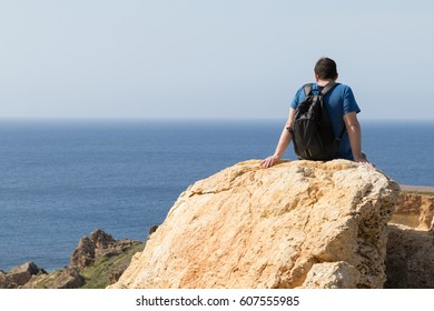 Male adult man in blue t-shirt and rucksack sits on rock overlooking beautiful golden sandy beach and blue mediterranean sea at Ghajn Tuffieha, Malta on a bright sunny day