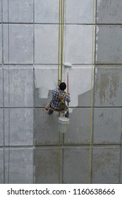 A male adult painting a building wall sitting on a swing