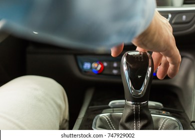 Male adult person sitting inside a new modern car, close up of hand almost touching a six-speed gearbox
