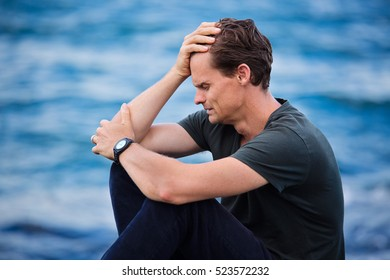 Male adult puts hand on head and looks very distressed and is suffering from depression and intense sadness, he is crying and sitting by the ocean.