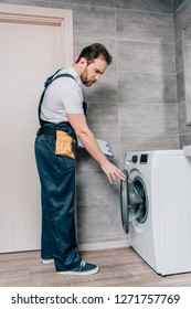 male adult repairman with toolbelt and clipboard checking washing machine in bathroom