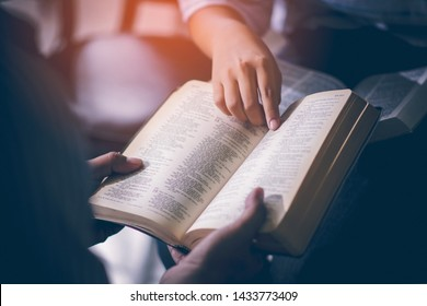 Male adults are reading the Holy bible by pointing to the character and to share the gospel to youth. The cross symbol, The books of the Bible, Concepts of Christianity.