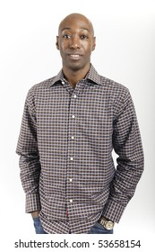 Male African American standing with hands in pockets wearing a check shirt