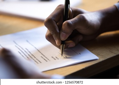 Male african hand signing financial contract concept, black businessman put write signature on legal corporate paper fill document form buy insurance loan, making business agreement, close up view
