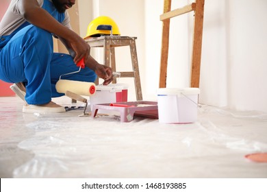 Male African-American decorator doing repair in room