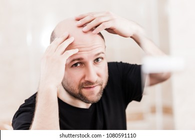 Male alopecia or hair loss concept - adult caucasian bald man looking mirror for head baldness treatment