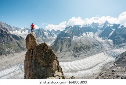 Male alpinist standing up on top of the mountain peak