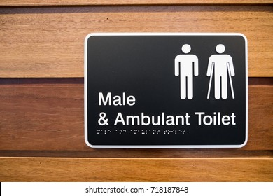 male and Ambulant Toilet sign with wooden background