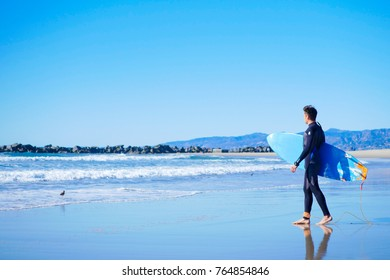 Male american surfer wearing full black wetsuit going to surf in Pacific ocean