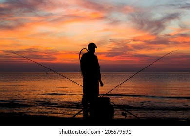 Male angler looking at the sunset after a day of angling.