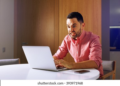 Male angry student work on computer touch pad, young angry business man use laptop sitting at wooden table of home, angry freelancer working on notebook at kitchen. angry entrepreneur and furious