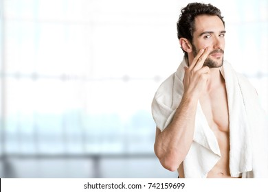 Male applying moisturizer to her face in a bathroom