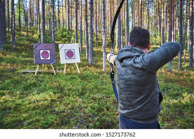 Male archer aiming at the bow target in the forest