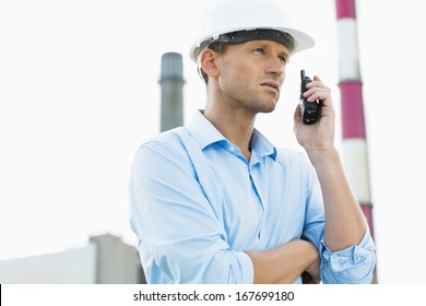 Male architect communicating on two way radio at site