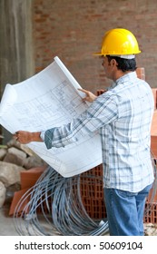 Male architect at a construction looking at blueprints