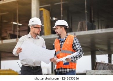 Male architect and developer discussing blueprints of an architect project at 