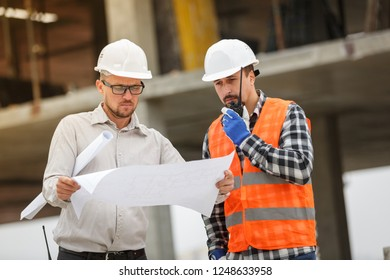 Male architect and developer with walkie talkie discussing blueprints of an architect project at 