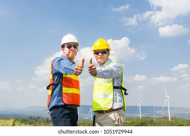 Male Architect and Engineer Smile and showing thumbs up together beside Wind Turbine power generator Site as Architecture Engineering Teamwork Attitude and Teamwork Concept.