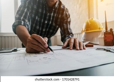 Architecte ou ingénieur masculin travaillant à la maison dessinant le projet de construction.