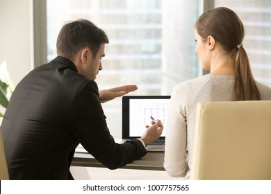 Male architect explaining details of project to female client while sitting at desk in front of laptop with house plan on screen. Realtor telling buyer about apartment features and benefits. Back view
