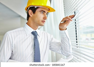 Male architect in helmet looking through window
