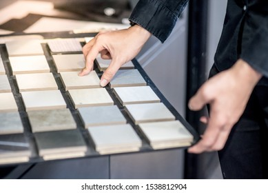 Male architect or interior designer hand choosing ceramic texture sample from swatch board in design studio. Floor and wall finishing material for architecture and construction industry. - Shutterstock ID 1538812904