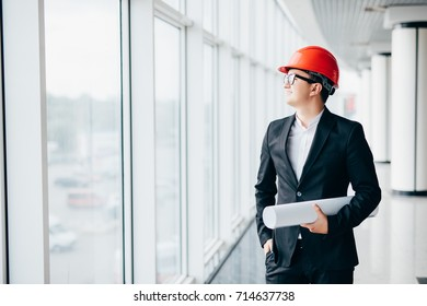 Male architect looking at blueprints in hamlet near panoramic windows