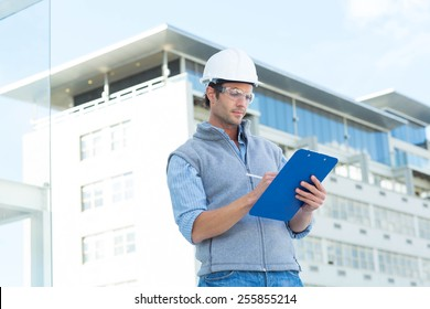 Male architect writing on clipboard outside building
