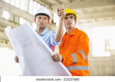 Male architects with blueprint working at construction site