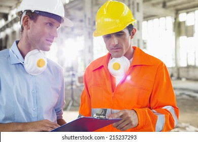 Male architects in protective workwear discussing at construction site