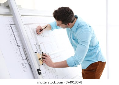 Male architects working on blueprints