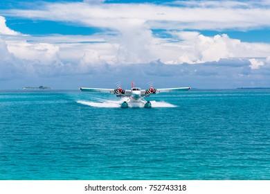 Male, Ari Atoll, Maldives - December 16. 2016: Seaplane of Trans Maldivian Airways landing in blue sea.