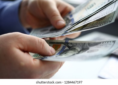 Male arm count hundred dollar bills closeup. Bribery accept backhander banknote venality laundering back scheme offshore company irs employee kickback collusion lobby gift compensation contribution