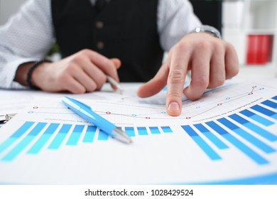 Male arm hold silver pen and point finger in financial graph