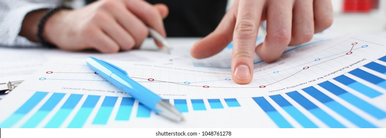 Male arm hold silver pen and point finger in financial graph solve and discuss problem closeup. Fresh view at situation board council sale adviser examine advisor profit audit job market irs concept